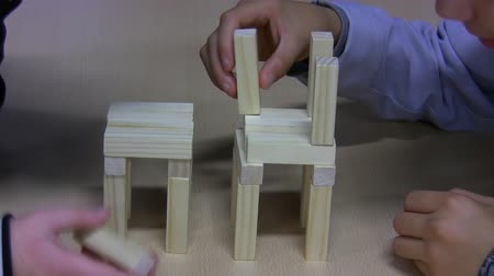 bloklar : Two boys together constructing the tower from wooden  construction bricks Stok Video
