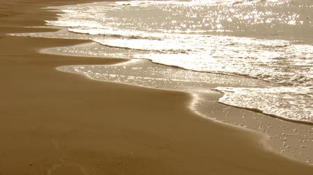 пена : Sea waves splashing on a sandy beach, shining and shimmering sunlight flickers