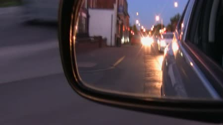 outside view : Side mirror rear view of street with houses, cars and streetlights from moving car at night.