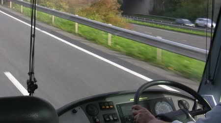 inside bus : Bus driver is driving a bus. View of steering wheel, hands and motorway on the move Stock Footage