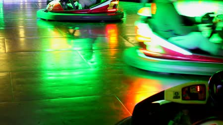 otopark : Bumper cars are moving fast and bumping into each other in a colorful colourful amusement park Stok Video
