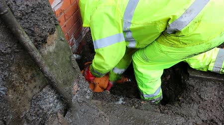 hasznosság : Professional plumber in bright waterproof clothing is working outside the house. He is fitting  a new drainage bottle gully onto the pipe in the ground.