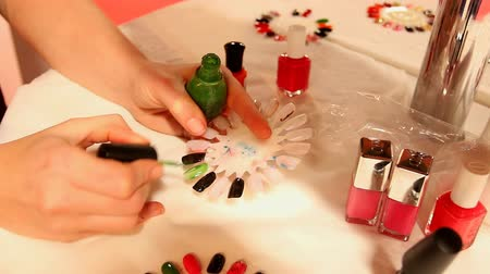 unha : Nail technician putting on nail varnish on artificial nails at the beautician salon Stock Footage