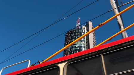 architecture and urbanism : View of moving trolleybus, overhead lines and skyscraper glass reflections against blue sky in a big city on a sunny day