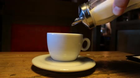 диабет : Cafe scene. Close up of hand holding sugar dispenser pouring sugar into white cup on a saucer with steaming tea or coffee