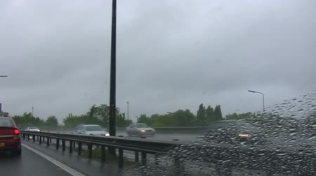 london england : Example of left hand drive. Busy motorway in the United Kingdom where traffic flow is left-hand. View from inside of moving car. Stock Footage