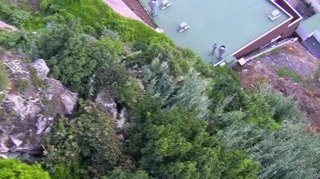 traverse : Birds eye view of a mountain slope with private red and industrial green house roofs and cars on the road