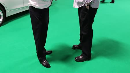 sala de exposição : Two businessmen talking at a car showroom standing on the bright green floor with a brand new white car behind. Vídeos