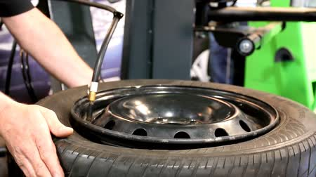 ar : A vehicle tyre tire is being filled with air at the service station by mechanic