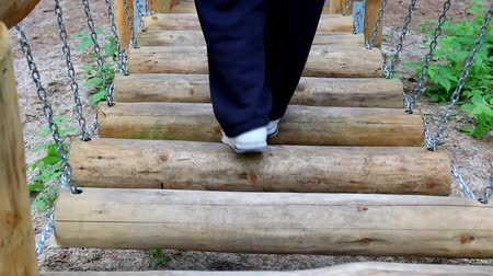 obstacles : Legs of man or woman slowly walking obstacle course, swinging logs on chains in the forest, park or playground making rattling sound.