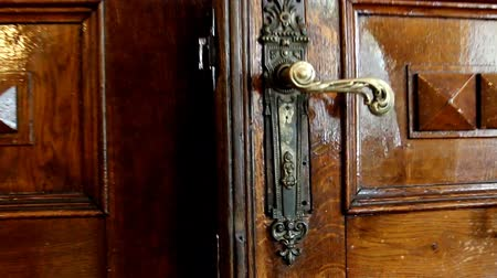 drzwi : Old wooden vintage door with brass handle and shiny dark brown decor. Somebody is going to the door, opens it revealing a very bright doorway. Wideo