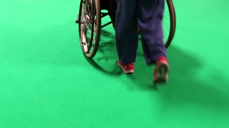 rokkant : Rear view of a woman pushing disabled or old person in a wheelchair isolated on green background. Stock mozgókép