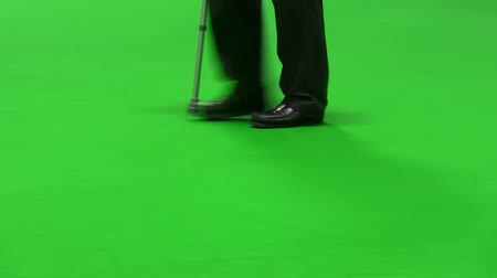 bengala : Man with walking stick limping isolated on green background Stock Footage