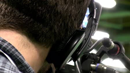 стрельба : Back of the head of professional tv camera operator with headphones at work. Стоковые видеозаписи