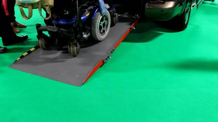 wheelchair ramp : Electric scooter for disabled driving out of a car or van using ramp isolated on green background.