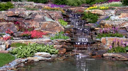 waterfall cascading into pool : Man-made back garden waterfall cascade on the rocks with water flowing into the pond surrounded by flowers and other flora on a windy day. Stock Footage