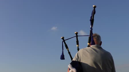 felvidéki : View from behind of an old man playing bagpipes outdoor against blue sky