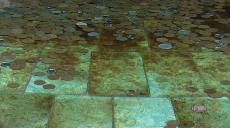 illúzió : Copper and nickel coins at the bottom of tiled fountain with crystal clear rippled water making illusion of coin movement. Dropped coin makes a nice splash and settles down at the front left of the frame.