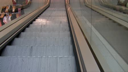 лифт : View of moving down empty escalator at the clothes section of the department store.