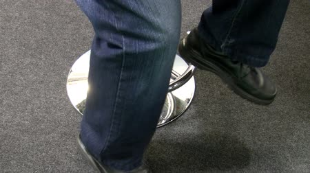 lower part : Lower part of the body; man wearing jeans and black shoes comes to the shiny leg of bar stool, sits on the chair, after while stands up and leaves the frame. Stock Footage