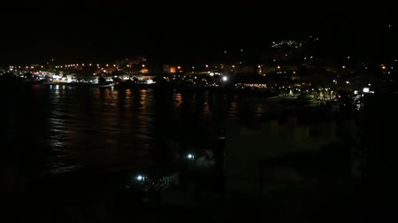 dark bay : Night view of the city on the hill with some cars moving and lights reflections on the rippled sea water in the dark. Stock Footage