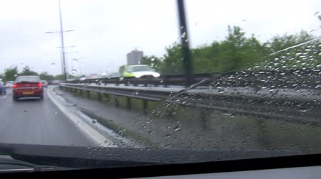 wipe away : Car front window view of moving vehicle. Windscreen wipers wipe away rain drops when driving in Great Britain on motorway on a rainy day.