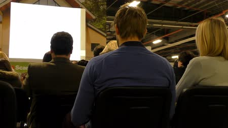oturum : Rear view of people sitting and listening at the business presentation with white blank screen in front