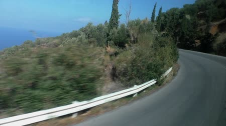 high speed road : Windscreen view of moving bus on coastline asphalt road winding high in the mountains with blurry roadside bushes, cypress trees, rocks, blue sky and sea in a distance in a hot country