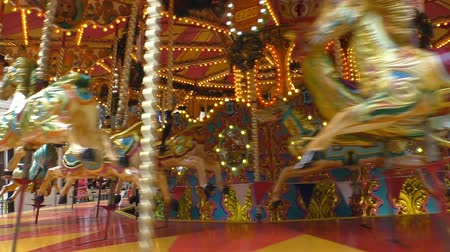 карусель : Old carousel spinning outdoors almost empty with only few people and children riding vintage horses Стоковые видеозаписи