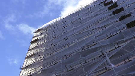 állványzat : Closer look at the building under reconstruction with scaffolding covered with safety nets waving in the wind and white clouds crossing bright sky above