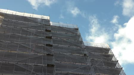 állványzat : Construction site safety netting waving in the wind and white clouds moving across the blue sky above block of flats under reconstruction
