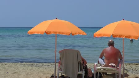 emekli : An elderly couple under orange beach umbrellas enjoying beautiful view of turquoise color sea. A man with brown red suntanned back is sitting on his sunbed next to woman lying on her sunbed Stok Video