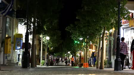uliczka : People walking, teenagers riding on bicycle in the pedestrian shopping area of the city center centre in Greece at night Wideo