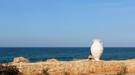 греческий : Simple background illustrating Greece - amphora reminds about rich culture and history of the country, clear sky and turquoise sea - beautiful holiday weather, yellow brown stone wall and specific plants - tropical weather