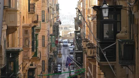 side view : Old tall buildings with balconies on narrow side street of Valletta city centre center, capital of Malta