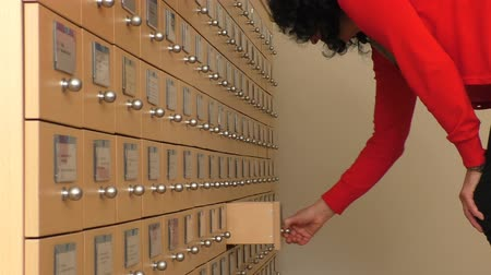 dosyalama : Woman in the office searching for a file by opening card index cabinet drawers