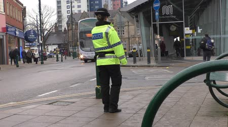 polícia : SALFORD, GREATER MANCHESTER - UK, April 2015: Policewoman patrolling at Eccles bus station in the town centre center in spring.