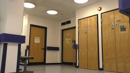 bekleme : Establishing shot of hospital waiting room with many wooden doors with various hazard and no entry signs. Zooming onto the door with x-ray warning sign, radiation symbol.