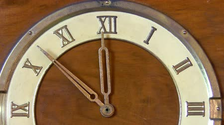 arife : Old wooden vintage clock with roman numbers. Time stops at 12 hours midnight or noon