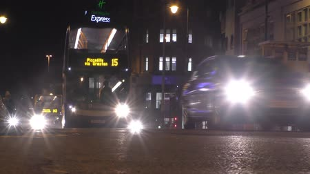anglia : MANCHESTER, UNITED KINGDOM - JANUARY 14, 2016: Low angle shot of city transport at night on Oxford street. Double-decker buses and cars with glaring headlights passing the camera Stock mozgókép