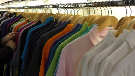 clothing : Selection of colorful colourful t-shirts on wooden hangers swinging on the rack at a clothing store, customer looking through trying to choose one
