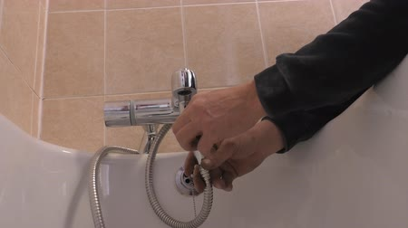 plumber : Professional plumber fitting hand shower hose  in the bathroom