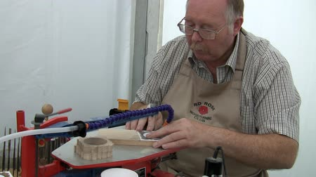 velo : SOUTHPORT FLOWER SHOW, UNITED KINGDOM - AUGUST 19, 2012: Senior craftsman, member of Red Rose Woodturning club in Lancashire cutting wooden souvenir fine detail on electric scroll jig machine