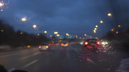 rainy : Blurred driver view of motorway and transport driving in a rain, focus on wet windscreen