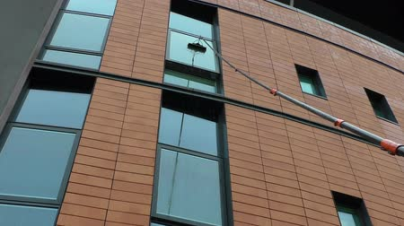 temizleme maddesi : Professional window cleaner wearing high visibility vest washing modern building exterior windows with water fed extending pole system