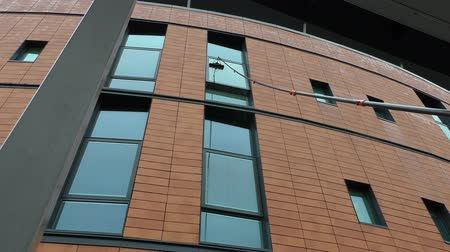 arruela : Professional window cleaner standing on the ground using telescoping water fed pole washing system is cleaning modern high rise building window