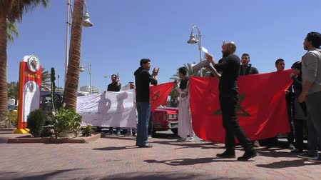 sacked : AGADIR, MOROCCO - MARCH 25, 2016: Sacked restaurant Havana workers protesting holding national flag, slogans, Kings portrait and chanting Stock Footage