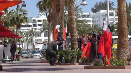 sacked : AGADIR, MOROCCO - MARCH 25, 2016: Group of made redundant restaurant employees chanting slogans in front of restaurant Havana in the street