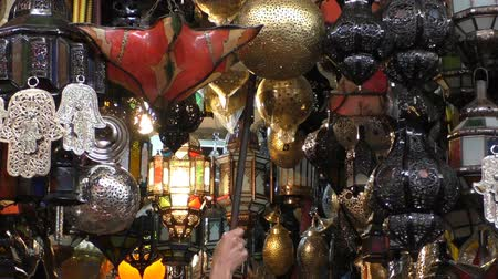 марокканский : Man using a pole to hang traditional Arabic style lamp in the market of Marrakesh Marrakech.