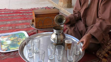 demlik : Moroccan Berber man wearing traditional clothes sitting on the pillow on concrete floor inside his house is making tea for his guests